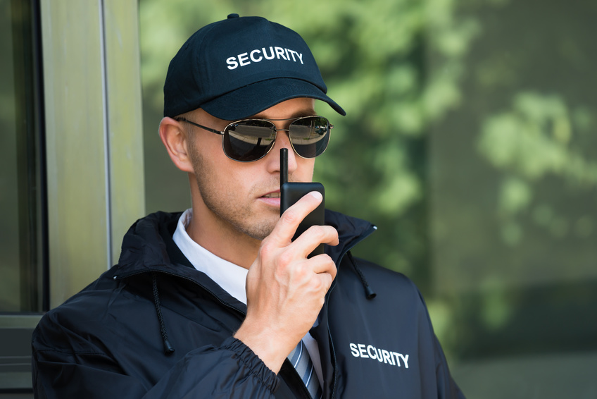 Portrait Of Young Security Guard Talking On Walkie-talkie
